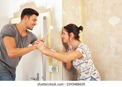 Young couple having fun while renovating the new dwelling