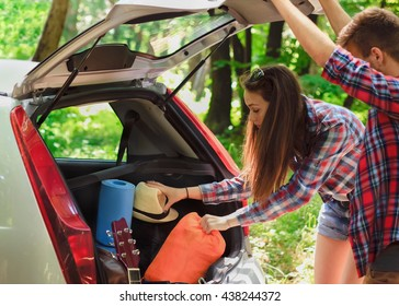 The young couple is having fun while unpacking camping equipment Forest camping, hiking.
