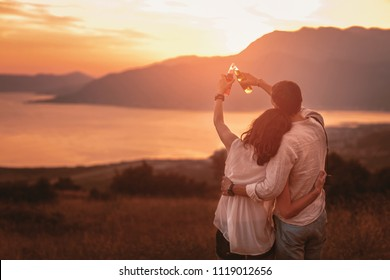 Young couple having good times in nature looking at the sunset on Boka Bay.