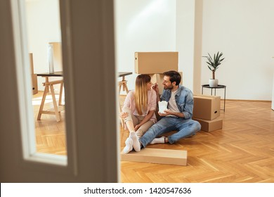 Young couple having lunch break during moving into their new home
