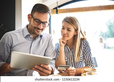 Young couple having online shopping by tablet and enjoying coffee.