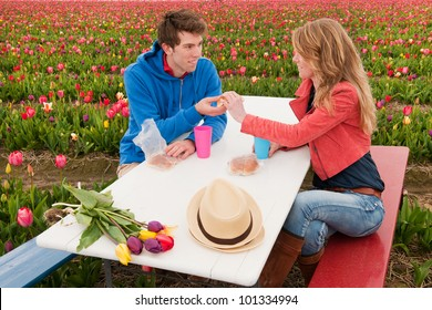 Young couple is having picnic in Dutch flower fields