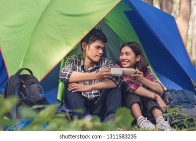 Young couple having a picnic at forest, Asian couple sitting and drinking coffee in front of the tent in nature