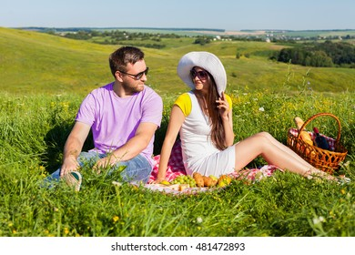 Young couple having picnic on the meadow