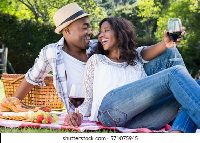 Young couple having a picnic in the park on a sunny day