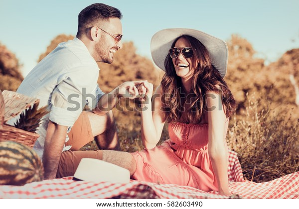Young couple having a picnic in the park on a sunny day.