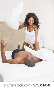 Young couple having pillow fight on the bed