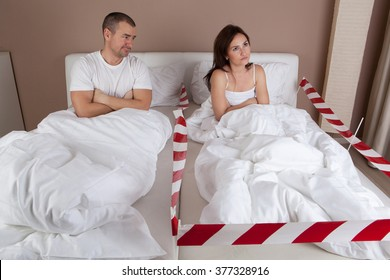 Young couple having problem. Angry woman lying separately from husband on the bed