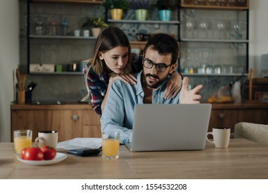 Young couple having problems with paying their bills over Internet