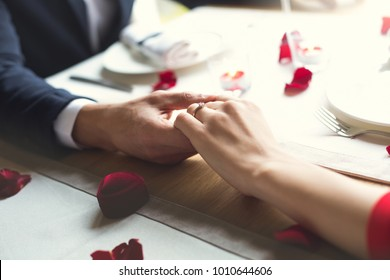 Young couple having romantic dinner in the restaurant wearing a proposal ring close-up
