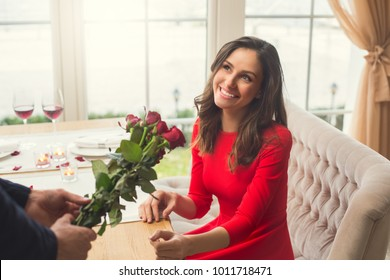 Young couple having romantic dinner in the restaurant giving flowers