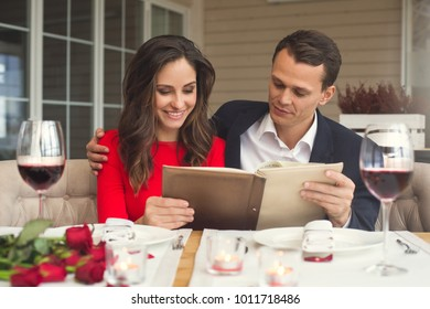 Young couple having romantic dinner in the restaurant holding menu concentrated