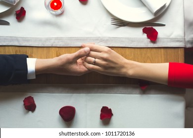 Young couple having romantic dinner in the restaurant wearing a proposal ring top view