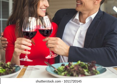 Young couple having romantic dinner in the restaurant cheers close-up