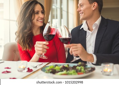 Young couple having romantic dinner in the restaurant sitting together holding wine glasses front view