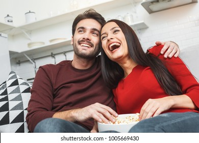 Young couple having romantic evening at home together watching comedy show