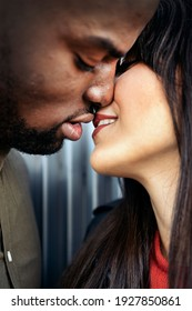 Young couple having romantic moments together in the street. Multicultural couples concept