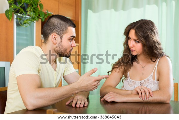 Young couple having serious conversation in home interior
