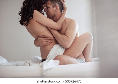 Young couple having sex in bedroom. Sensual lovers making love in bed.
