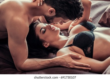 Young couple is having sex, lying on bed at home, man tenderly kissing his woman