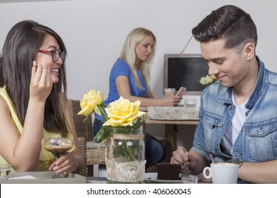 Young couple having smalltalk in cafeteria while blonde woman has a phone call