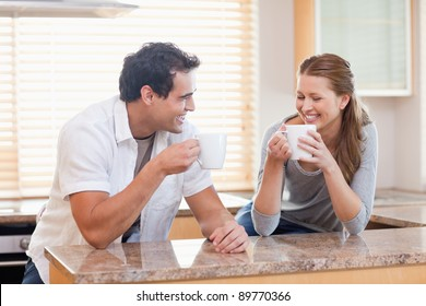 Young couple having some coffee in the kitchen