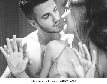 Young couple having tender and sexual moments inside box shower - Two lovers enjoying time together with kisses and hugs  - Love and sex concept - Focus on man eye - Vsco black and white filter