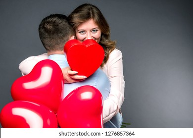 Young couple with heart shaped red balloons near grey wall.