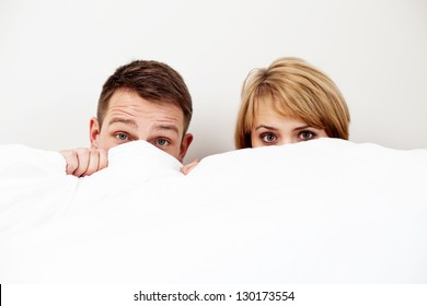 Young couple hiding behind blanket in bed