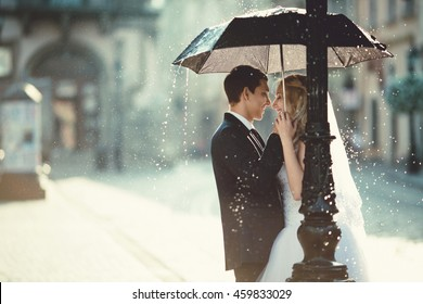young couple hiding from the rain