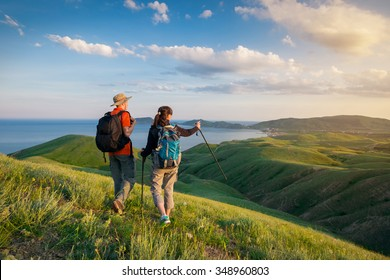 Young couple hike in the mountains. A man and a woman walking and looking at the beautiful landscape.