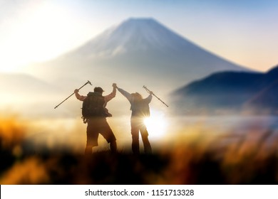 Young couple hikers climbing up hike on the peak of rocks mountain near mountain fuji  during sunrise ,concept for success, winner and leadership .