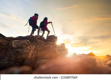Young couple hikers climbing up hike on the peak of rocks mountain  during sunset ,concept for success, winner and leadership .