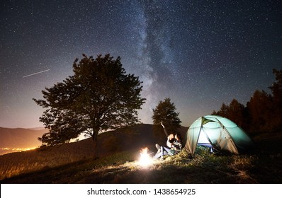 Young couple hikers having a rest at campfire beside camp and tourist tent. Man pointing at night sky full of stars and Milky way. On the background starry sky, mountains, big tree and luminous town