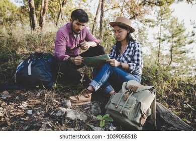 Young couple hikers with and looking on the map to find a way. Got lost in the forest. Outdoor, Travel relax, Holiday and vacation, Travel, Love and relations, Travel hiking.