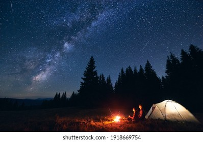 Young couple hikers sitting near bright burning bonfire and illuminated tourist tent, enjoying camping night together under dark sky full of shiny stars and bright Milky Way, warm summer evening.
