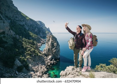 Young couple hikers taking selfie photo on phone  in the mountains background the sea. Beautiful Man and Woman traveling active adventure vacations.