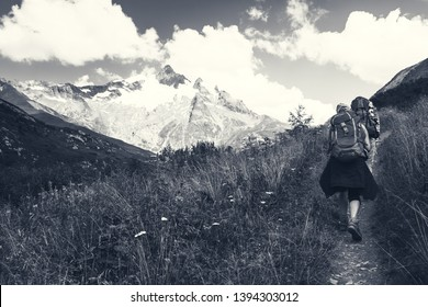 Young couple hiking in French Alps in summer. The Aiguille des Glaciers, mountain in the Mont Blanc massif. View From Chapieux valley, Savoie, France.  Black white monochrome photo.