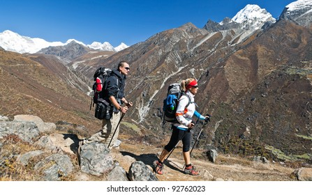 Young couple hiking in himalayas mountains in Nepal. Young people traveling in Asia, trekkers on trail in wilderness.