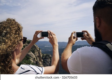 Young couple hiking in the mountains taking a picture of landscape on smart-phones