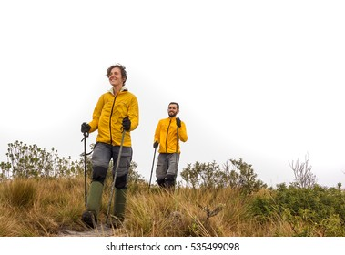 Young couple hiking and smiling with trekking poles and boots