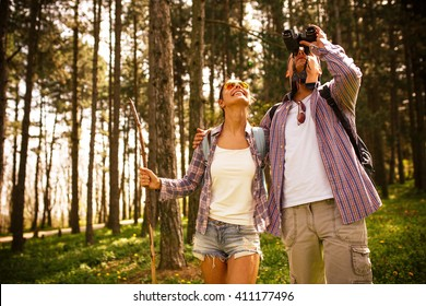 Young couple hiking trough forest and watching birds.Ornithology .
