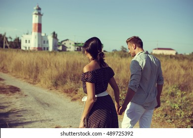 young couple hipster indie style in love walking in countryside, holding hands, lighthouse on background, warm summer day, sunny, bohemian outfit, vintage bag with flowers. Copy space