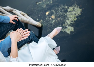 A young couple hold hands. lovers guy and girl walk in the summer in nature. The bride and groom. Hands close-up