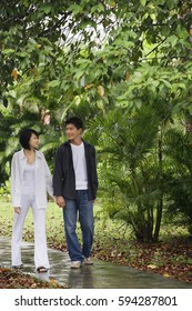 A young couple hold hands and stroll down a garden path together