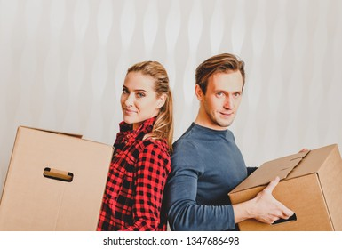 Young couple holding boxes because moving into their new home.