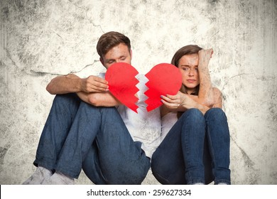 Young couple holding broken heart against grey background