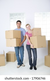 Young couple holding cardboard boxes. They're smiling and looking at camera. Front view.