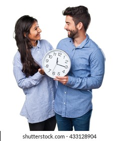 young couple holding a clock
