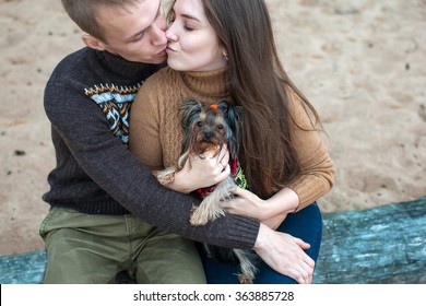 young couple holding a dog in her arms on the rocky beach